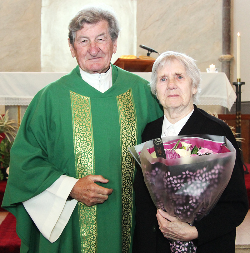 Bridie McHugh is presented with a bouquet of flowers to celebrate her 80th birthday