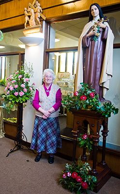 Joyce French standing next to the two floral arrangements she created as a tribute to her husband David.