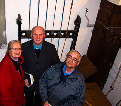 Ruth and John Werbiski with Canon Edmond Gubbins in front of the bell ropes