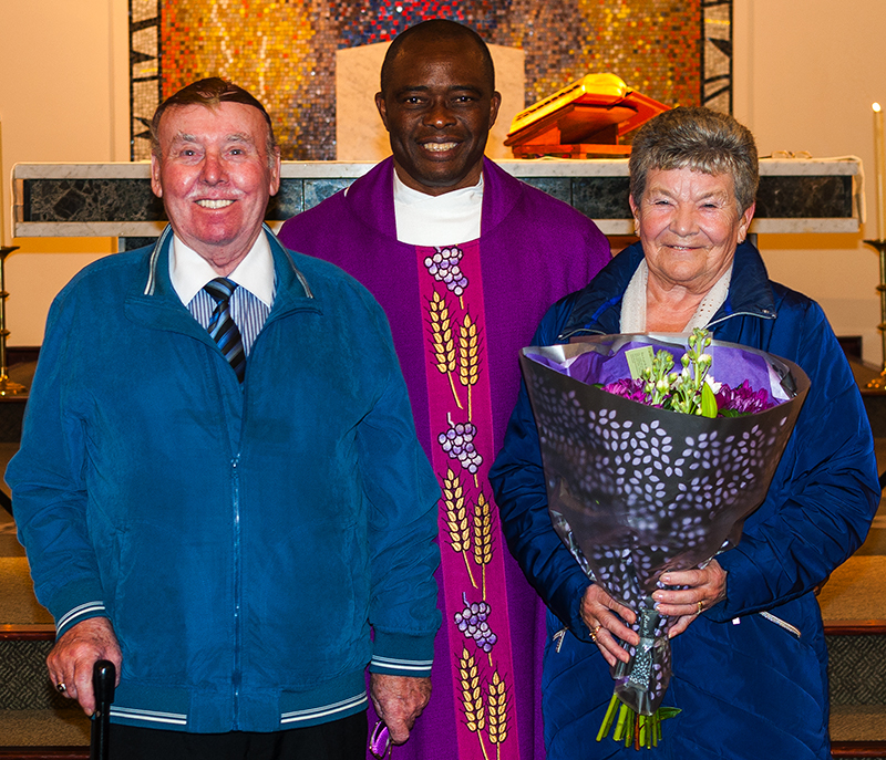 Thomas and Mary Pepper receive a bouquet from Assistand Priest Fr. Damian.